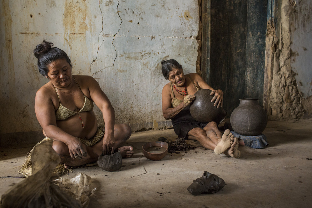 """My grandmother taught me how to make ceramics when I was a child,"" said Eduarda Amélia de Jesus, 74, right, at her home with her daugher, Maria Iracema Jesus de Souza, an old colonial home where she makes pottery and stores her clay, tools and finished pots, at Aldeia Mirandela, in Ribeira do Pombal, in the state of Bahia, Brazil, on Wednesday, April 13, 2016. Dona Eduarda did want to say her age, but we guess its about 74-years-old. She is the wife of the tribe chief, Lazaro Gonzaga de Souza, 76. They wear their native garb made out of grass in honor of Día do Índio, or Indigenous Day, celebrated on April 19."