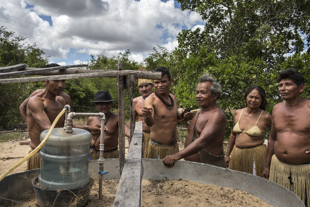Some members or the Kiriri tribe look at a biodigester, built four years ago, at a home of one tribeman, at Aldeia Marca‹o Kiriri, near Ribeira do Pombal, in the state of Bahia, Brazil, on Tuesday, April 12, 2016. The system breaks down cattle manure and converts it into methane gas to be used as energy for cooking stoves. The byproduct is then used as fertilizer.