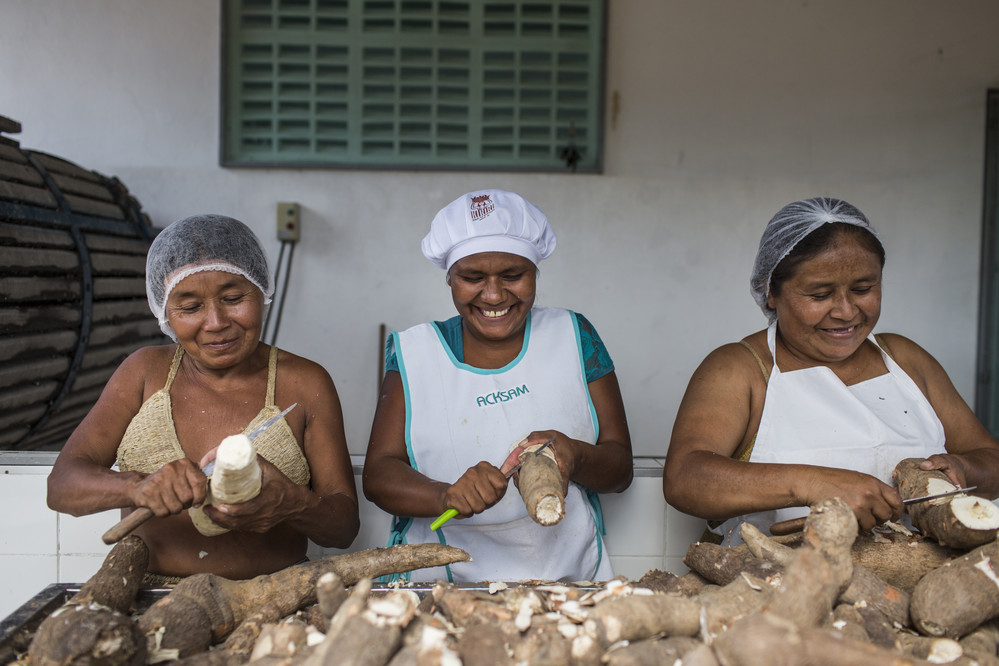 Maria do Carmo Vieira Araujo, 50, Ednalva Maria de Jesus, 31, and Dilma Jesus Panteleon, 40, peel cassava roots together at the cooperative, at Aldeia Marcação Kiriri, near Ribeira do Pombal, in the state of Bahia, Brazil, on Tuesday, April 12, 2016. The program enables women to work, socialize and sell good to support and sustain the tribe. The IFAD-funded Rural Sustainable Development Project in the Semi-arid Region of Bahia (Pro-Semiárido) has been working together with the Kiriri people to allow them to use their traditional knowledge and traditions as a foundation upon which to build their livelihoods.